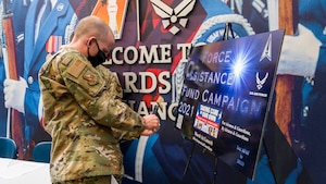 "Brig. Gen. Matthew Higer, 412th Test Wing Commander, scans the QR code for the Air Force Assistance Fund on his cell phone at Edwards Air Force Base, California, March 22. The campaign, titled ""For Airmen & Guardians, By Airmen & Guardians,"" runs until April 30. (Air Force photo by Giancarlo Casem)"