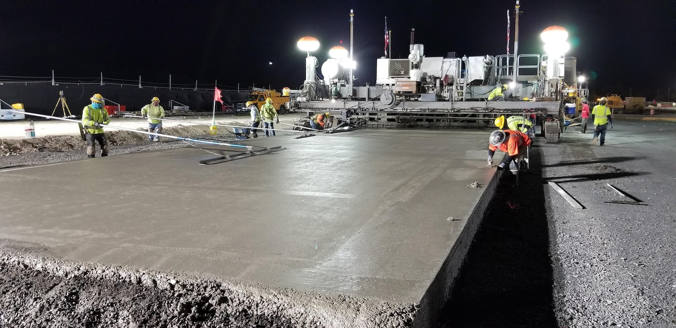 Sub-contractors for Kiewit smooth the cement surface of the new F-22 Fighter Alert Facility taxiway during a night paving Feb. 23 at Joint Base Pearl Harbor-Hickam.  During the five-hour-plus construction session the 40-ton crawler-type concrete finisher machine cast more than  360 cubic yards of Portland Cement Concrete Pavement (PCCP) for the taxiway.