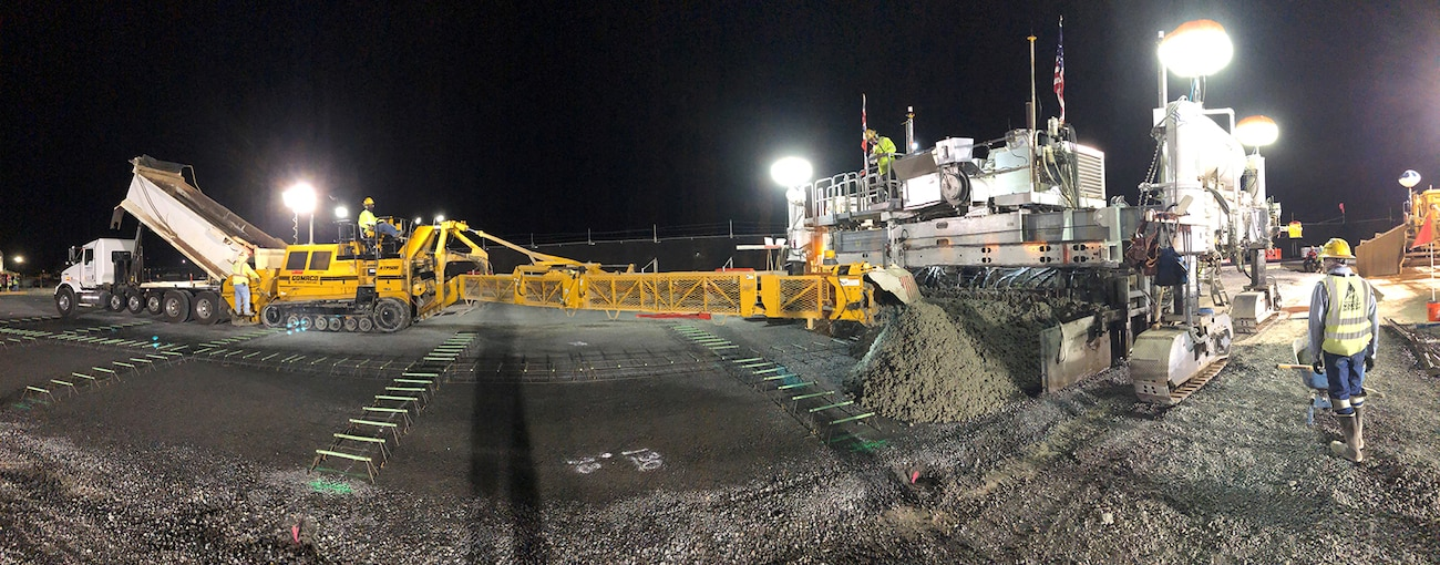 A panoramic view of F-22 Alert Fighter taxiway construction sub-contractor Kiewit conducting a night paving Feb. .23 at Joint Base Pearl Harbor-Hickam.  During a five-hour-plus construction session the 40-ton crawler-type concrete finisher machine cast more than  360 cubic yards of Portland Cement Concrete Pavement (PCCP) for the taxiway.