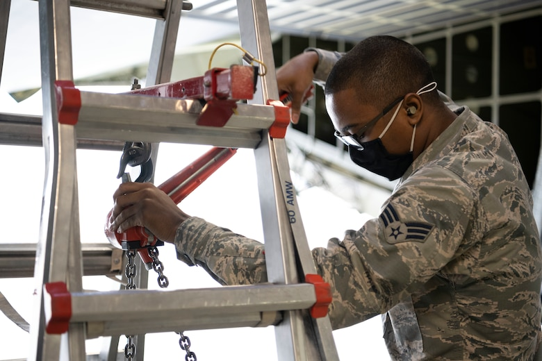 Senior Airman Saajaadeen Jeffries, 60th Aircraft Maintenance Squadron crew chief, lowers a cargo winch on a C-5M Super Galaxy March 18, 2021, at Travis Air Force Base, California. Travis Airmen collaborated with the Air Staff Logistics Directorate's Tesseract team and key partners from the C-5 program office to implement commercial maintenance practices in scheduling and completing maintenance around flying demands. (U.S. Air Force photo by Airman 1st Class Alexander Merchak)