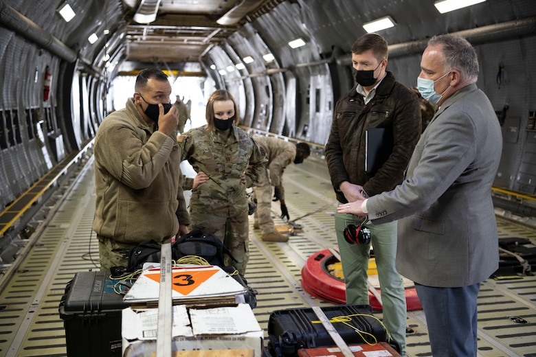 U.S. Air Force Master Sgt. Mario Hernandez, left, 60th Aircraft Maintenance Squadron home station flight chief, speaks with Steve Conley, second right, and Erik Klein, right both senior research associates at Georgia Tech Research Institute, during a home station check inspection development initiative March 18, 2021, at Travis Air Force Base, California. Airmen collaborated with the Air Staff Logistics Directorate's Tesseract team and key partners from the C-5 program office to implement commercial maintenance practices in scheduling and completing maintenance around flying demands. (U.S. Air Force photo by Airman 1st Class Alexander Merchak)