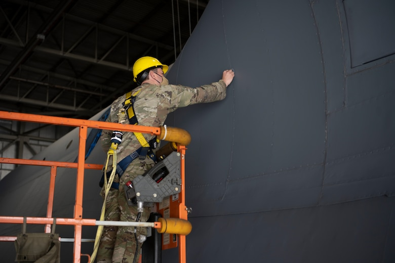 U.S. Air Force Staff Sgt. Joshua Wyatt, 60th Aircraft Maintenance Squadron home station check lead dock controller, marks areas to be fixed on a C-5M Super Galaxy during an exterior pylon inspection March 19, 2021, at Travis Air Force Base, California. Airmen collaborated with the Air Staff Logistics Directorate's Tesseract team and key partners from the C-5 program office to implement commercial maintenance practices in scheduling and completing maintenance around flying demands.  (U.S. Air Force photo by Airman 1st Class Alexander Merchak)