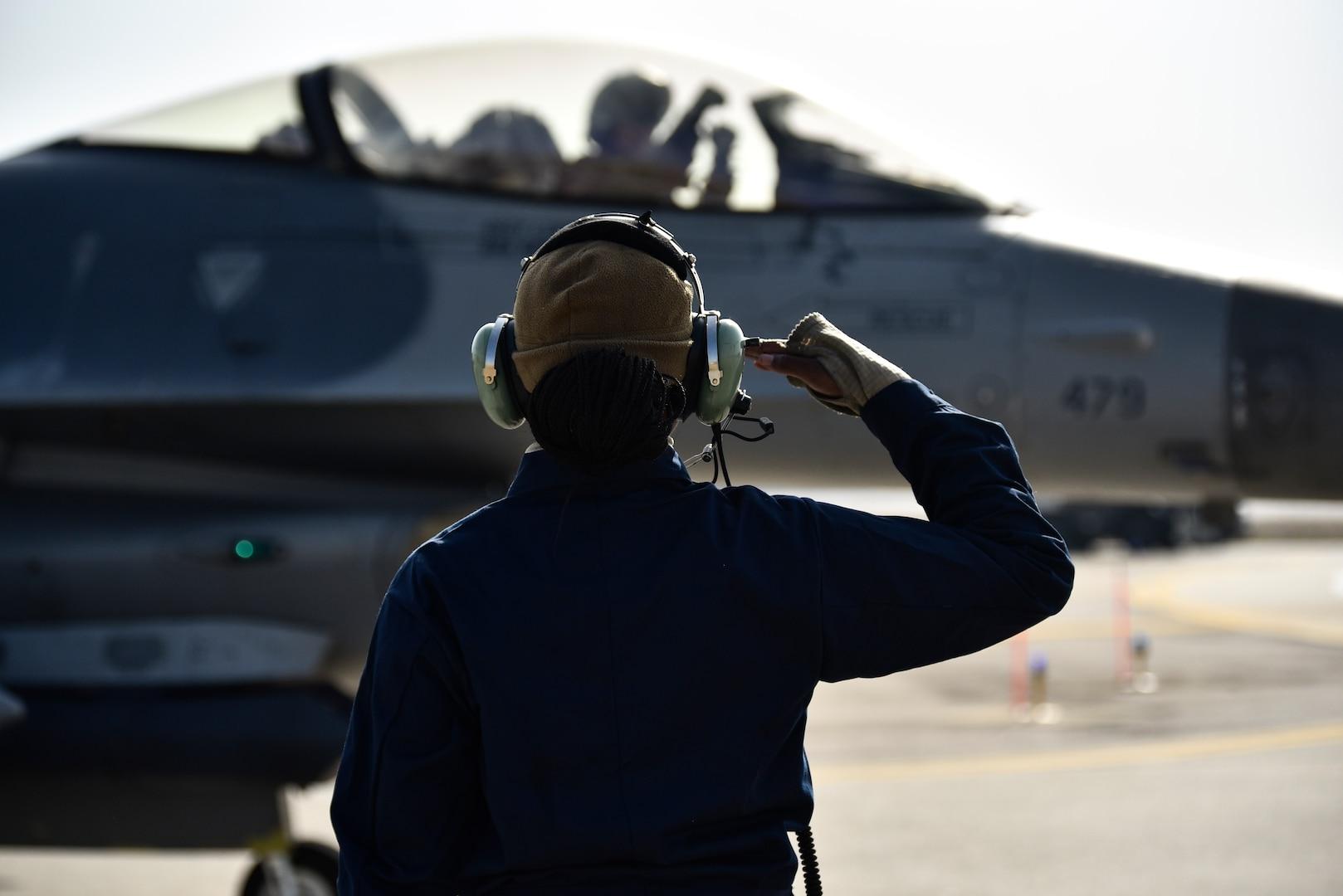 A crew chief salutes a pilot.