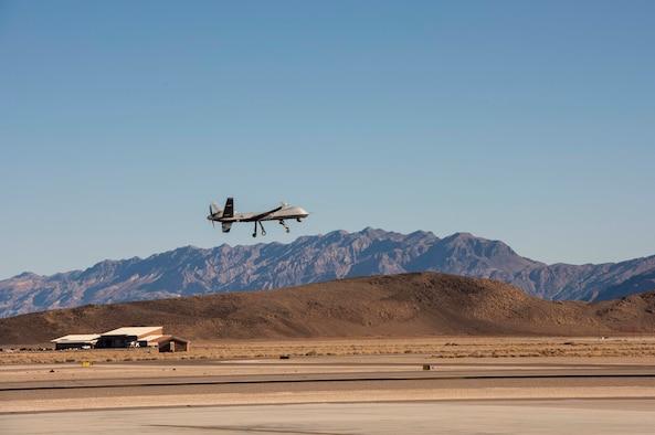 An MQ-9 Reaper flies over the base.