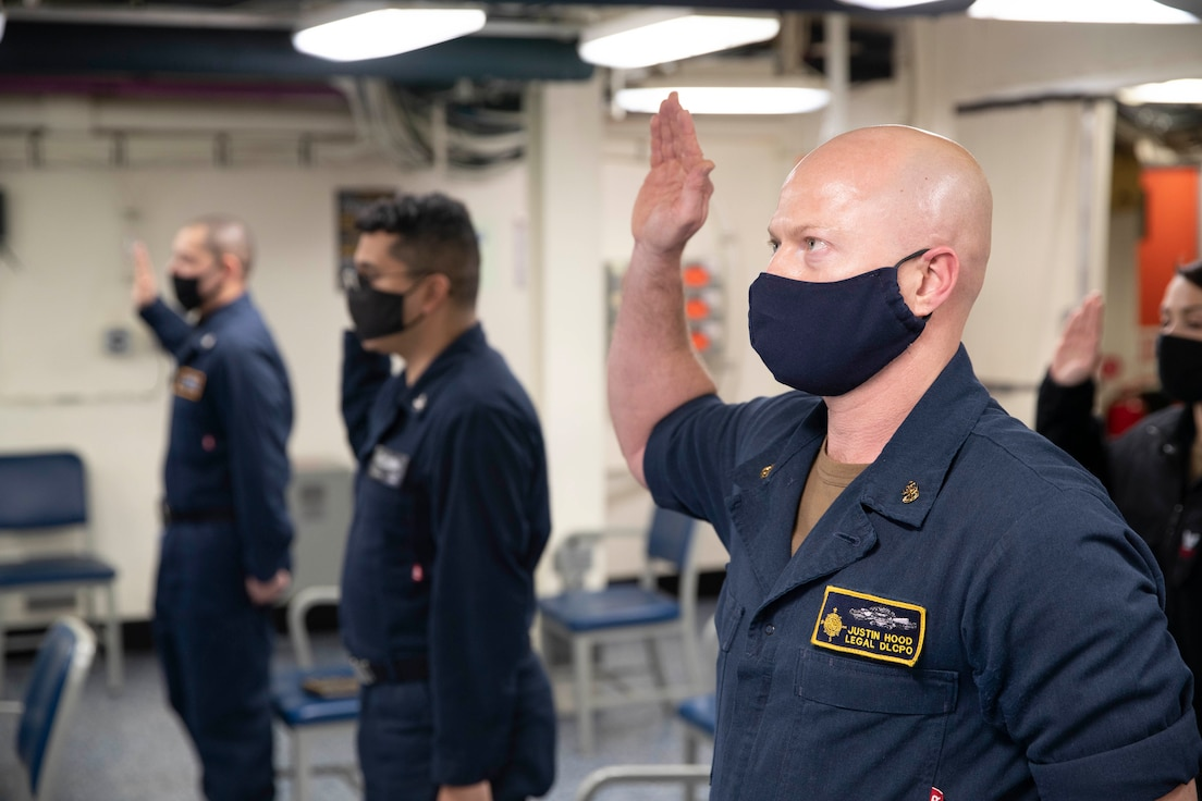 Chief Legalman Justin Hood, assigned to the aircraft carrier USS Gerald R. Ford (CVN 78), recites the oath of enlistment during an extremism standdown training.