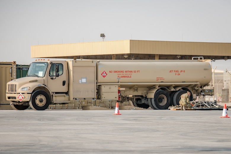 a refueling truck sits next to cargo being inspected by an Airman