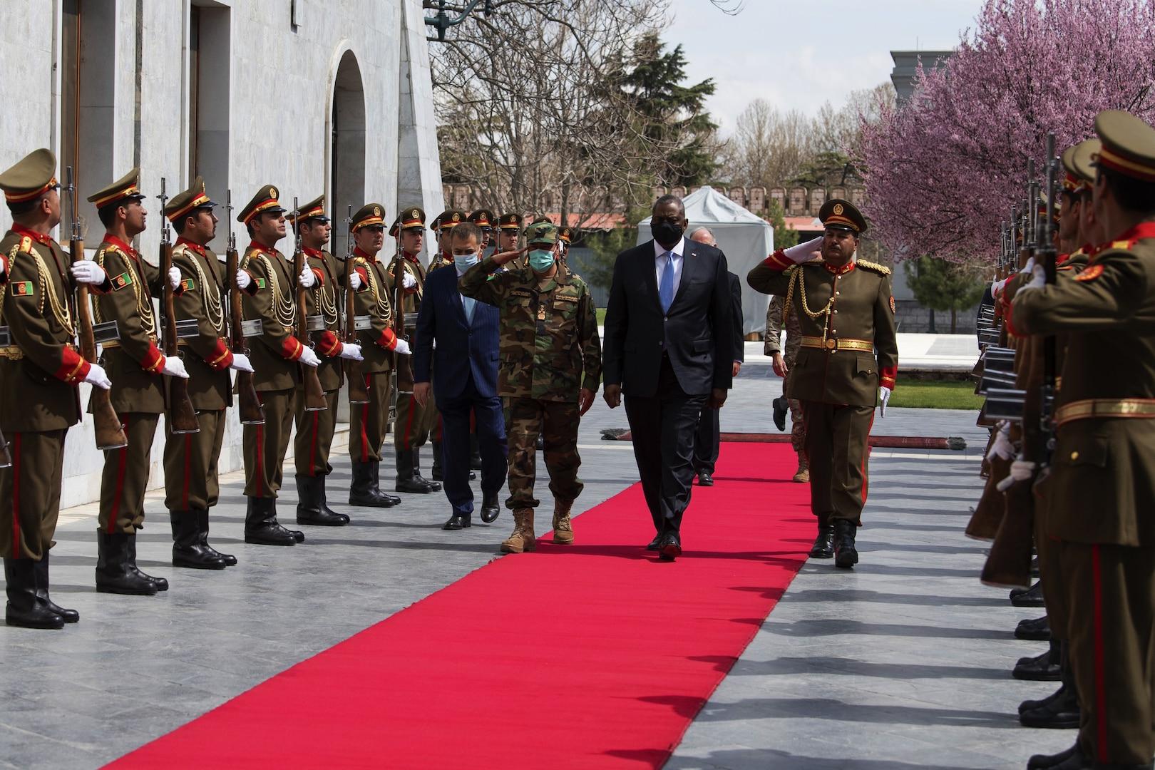 Defense Secretary Lloyd J. Austin III walks along a red carpet with military officials.
