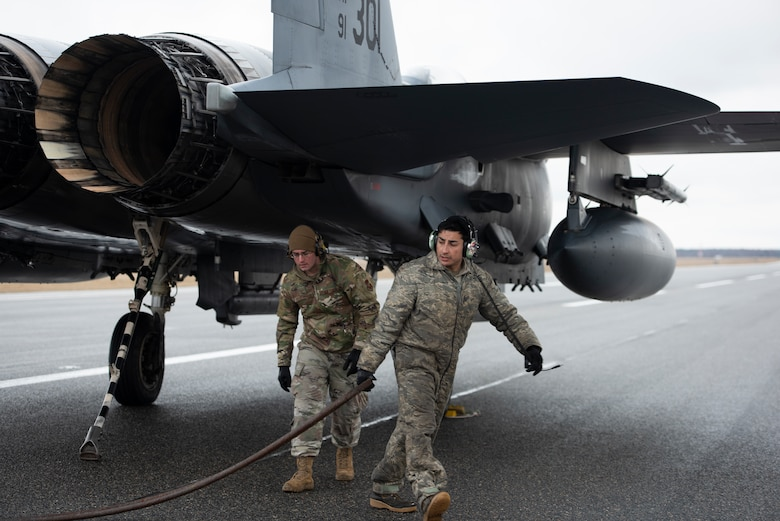 Airmen assigned to the 48th Aircraft Maintenance Squadron release the cable from the tailhook of a 492nd Fighter Squadron F-15E Strike Eagle during a Barrier Arresting Kit certification at Ämari Air Base, Estonia, March 17, 2021. During the test, the tailhook or arresting hook is dropped from the back of the F-15 as it fast taxis down the runway and catches the cable, which acts as a braking system to safely slow the aircraft during an emergency that would prevent the aircraft from performing a standard landing. (U.S. Air Force photo by Airman 1st Class Jessi Monte)