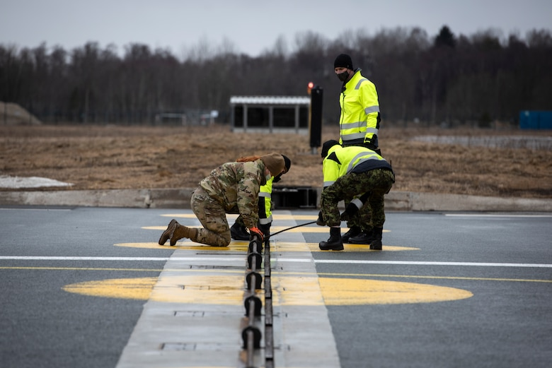 U.S. Air Force Airman 1st Class Chelsea Glasscock, 435th Construction and Training Squadron Aircraft Arresting System Depot apprentice, works with Ämari Air Base personnel to return the system to its starting position during a Barrier Arresting Kit certification at Ämari AB, Estonia, March 17, 2021. The BAK is certified annually to test the stability and effectiveness of the system, which acts as a braking mechanism to stop the aircraft in the event of an emergency that would prevent the aircraft from performing a standard landing. (U.S. Air Force photo by Airman 1st Class Jessi Monte)