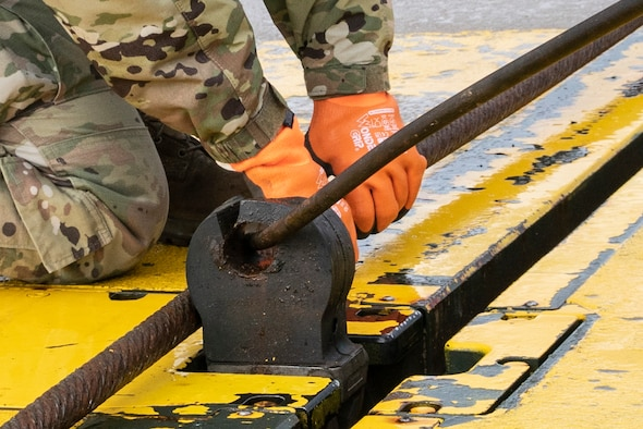 U.S. Air Force Airman 1st Class Chelsea Glasscock, 435th Construction and Training Squadron Aircraft Arresting System Depot apprentice, returns the system to its starting position during a Barrier Arresting Kit certification at Ämari AB, Estonia, March 17, 2021. An aircraft arresting system is in place to bring aircraft to a safe stop in the event of an emergency that would prevent the aircraft from performing a standard landing. (U.S. Air Force photo by Airman 1st Class Jessi Monte)