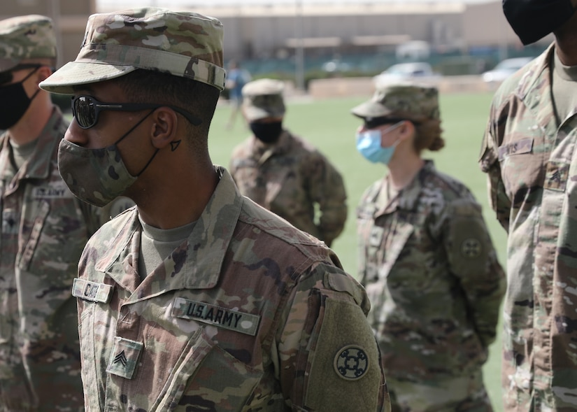 Army Reserve Sgt. Jeremie Cates, 310th Sustainment Command (Expeditionary), stands at parade rest at the March 21, 2021 recognition ceremony for the 328 U.S. and coalition military personnel who earned the Norwegian Foot March badge at Camp Arifjan, Kuwait. Cates earned his NFM badge when he completed the 18.6-mile course with a 25-pound ruck in 4 hours and 1 minute. (U.S. Army photo by Staff Sgt. Neil W. McCabe)