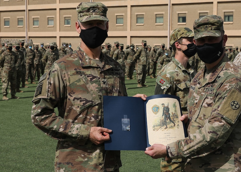 Army Reserve Col. Garrett Kolo, 310th Sustainment Command (Expeditionary), holds his Norwegian Foot March certificate presented to him by Army Reserve Brig. Gen. Justin Swanson, the commanding general of the 310th ESC, at the March 21, 2021 recognition ceremony at Camp Arifjan, Kuwait. Kolo, was the top finisher in the NFM when he crossed the finish line completing the 18.6-mile course with a 25-pound ruck in 2 hours and 52 minutes. (U.S. Army photo by Staff Sgt. Neil W. McCabe)