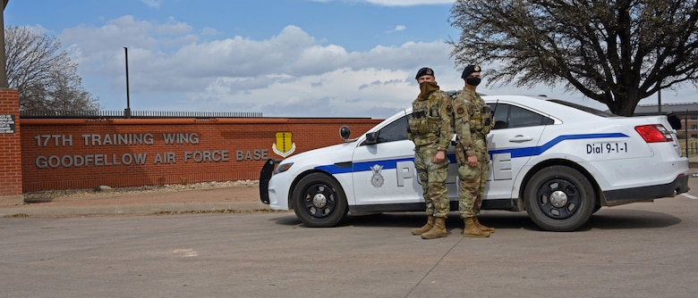 U.S. Air Force Airman 1st Class Damian Krogman and Airman 1st Class Brandon Krogman, 17th Security Forces Squadron installation entry controllers, stand outside of the Jacobson Gate, on Goodfellow Air Force Base, Texas, March 16, 2021. The two brothers are from North Dakota and were coincidentally assigned to this base. (U.S. Air Force photo by Senior Airman Abbey Rieves)