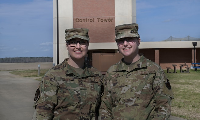 U.S. Air Force Senior Airman Laura O'Brien and Airman 1st Class Allison O'Brien, 14th Flying Training Wing air traffic controllers, stand together in front on the control tower, Mar. 11, 2021, on Columbus Air Force Base, Miss. The Airmen are sisters who share the same Air Force Specialty Code and are stationed at the same base. (U.S. Air Force photo by Airman 1st Class Jessica Haynie)