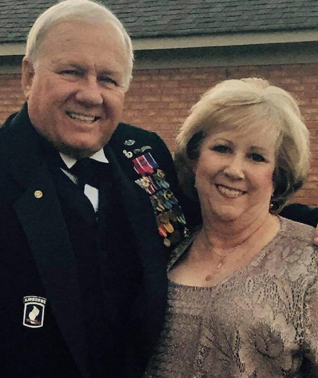 A man in an Army dress uniform hugs a woman.