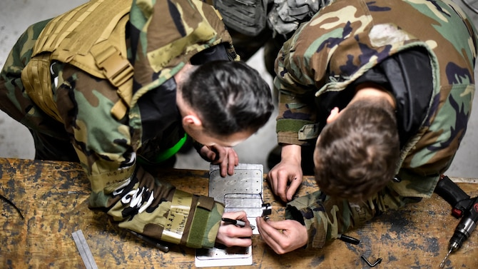 Airmen use tools to repair an aircraft component.