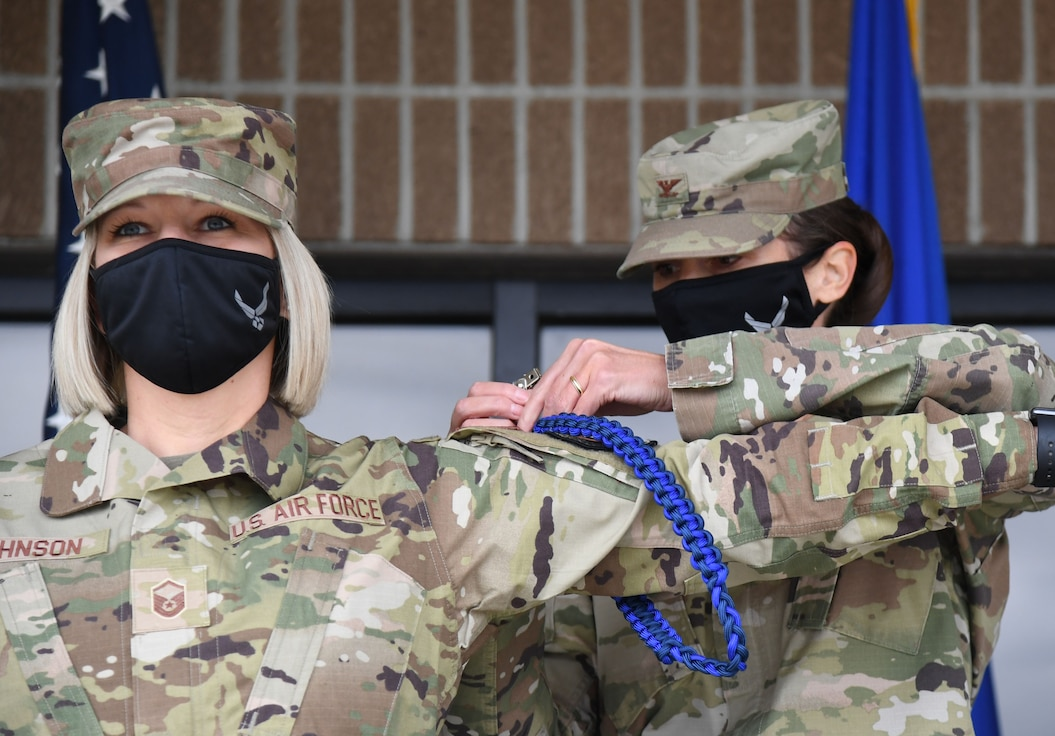U.S. Air Force Col. Heather Blackwell, 81st Training Wing commander, presents a Master Military Training Leader rope to Master Sgt. Jessica Johnson, 81st Training Support Squadron military training leader school instructor supervisor, outside the Levitow Training Support Facility at Keesler Air Force Base, Mississippi, March 19, 2021. The Master Military Training Leader Program, created at Keesler, was designed to distinguish the military training leaders who have mastered the demonstration, evaluation and reinforcement of military standards; exude military bearing and discipline while scheduling and conducting military training; and are key leaders among Airmen and their peers. (U.S. Air Force photo by Kemberly Groue)
