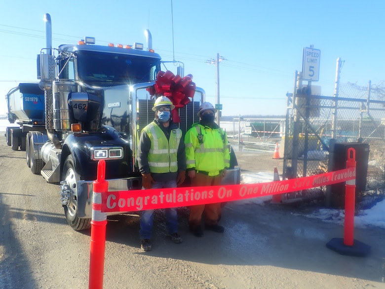 Luckey FUSRAP site team poses in front of a truck carrying contaminated soil,