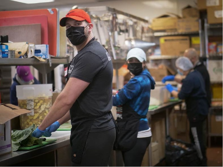 U.S. Air Force Staff Sgt. Jimmy Mrosko, an Air Guard and Reserve assignment technician, and his wife, Staff Sgt. Ashlee Sandefur, a Command Support Staff team member, both at Headquarters Air Reserve Personnel Center, prepares meals at Denver Rescue Mission Feb. 21, 2021, in Denver, Colo. Mrosko led the charge of developing a volunteer team from HQ ARPC in serving the 6,104 homeless persons of the Denver community on a bimonthly basis. (U.S. Air Force photo by Master Sgt. Leisa Grant/Released)