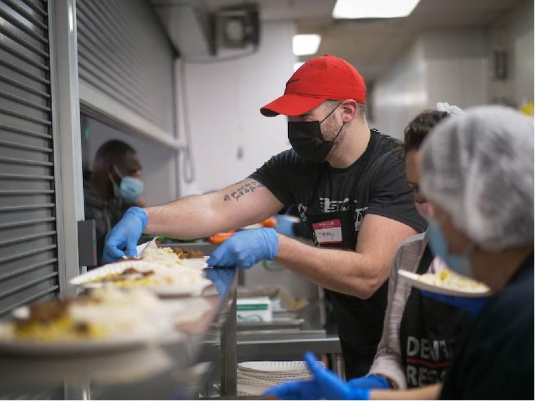"""U.S. Air Force Staff Sgt. Jimmy Mrosko, an Air Guard Reserve assignment technician at Headquarters Air Reserve Personnel Center, prepares meals at Denver Rescue Mission Feb. 21, 2021, in Denver, Colo. Mrosko said, """"these people are going through hard times, but I see the joy in their spirit."""" (U.S. Air Force photo by Master Sgt. Leisa Grant/Released)"""