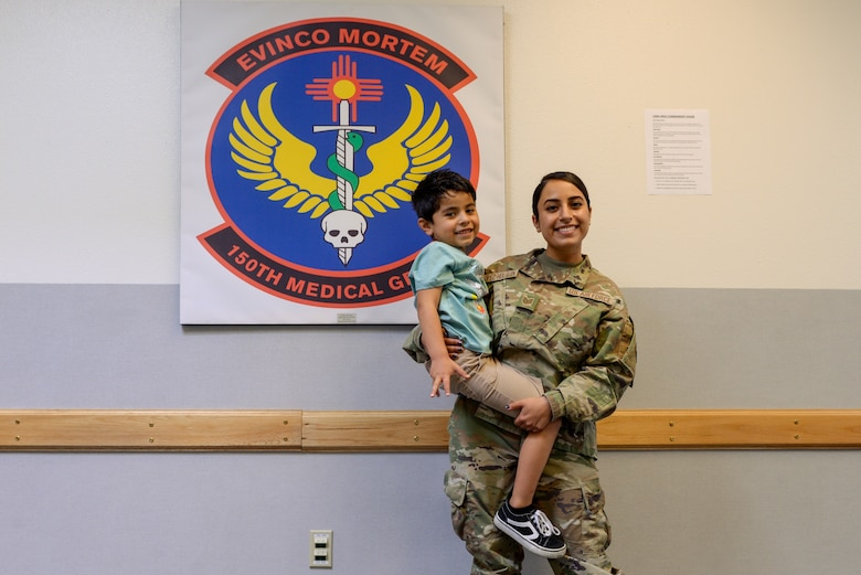 Tech. Sgt. Raven Lopez stands in front of the 150th medical group logo while holding her son in the lobby of the 150th medical building
