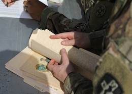 A volunteer leafs through Norwegian Foot March certificates after the March 21, 2021 recognition ceremony for the 328 U.S and coalition military personnel, who completed the NFM at Camp Arifjan, Kuwait. The Norwegian Army instituted the NFM in 1915, and the 18.6-mile with a 25-pound ruck completed under the age-group time limit event has become a tradition in the U.S. military, too. (U.S. Army photo by Staff Sgt. Neil W. McCabe)