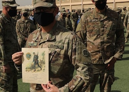 Army Reserve Staff Sgt. Justin McKay, who is deployed to Camp Arifjan, Kuwait, with the 310th Sustainment Command (Expeditionary), holds his Norwegian Foot March certificate after the March 21, 2021 recognition ceremony. McKay, a combat medic, said it was his third time completing the 18.6-mile course with a 25-pound ruck under the time limit for his age group. (U.S. Army photo by Staff Sgt. Neil W. McCabe)