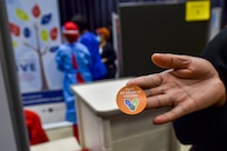 """In the foreground a hand holding an orange sticker that says """"I got my vaccine"""". In the background there are three medical personnel wearing personal protective equipment."""