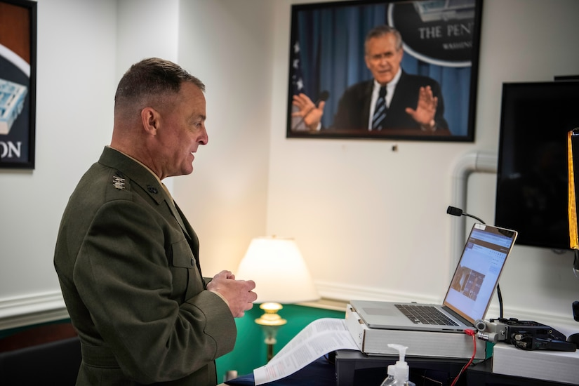 A man in a military uniform stands in front of a laptop computer.