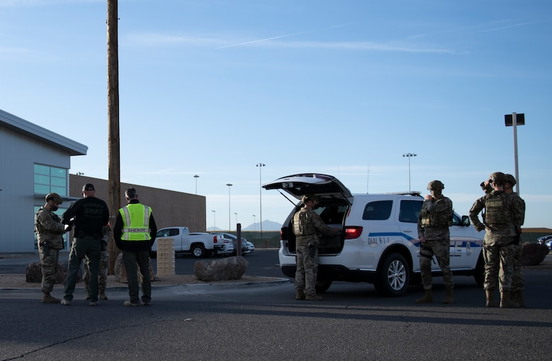 Airmen from the 56th Security Forces Squadron and officers from the Maricopa County Sheriff's Office train on the scene of an exercise Feb. 26, 2021, at Luke Air Force Base, Arizona. Security forces, MCSO and the Glendale Police Department all participated in the exercise, which evaluated the training, readiness and capability of Luke Airmen to respond to an active shooter. At the conclusion of the exercise, a real-world threat was announced and every law enforcement member participating in the exercise rapidly transitioned to the integrated response. Exercises ensure Airmen meet warfighting needs with a continuous drive toward more effective and efficient training, sharpening their real-world skills. (U.S. Air Force photo by Staff Sgt. Amber Carter)