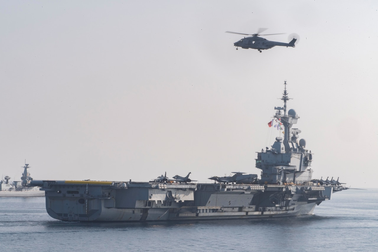 A helicopter flies over the French aircraft carrier Charles De Gaulle.