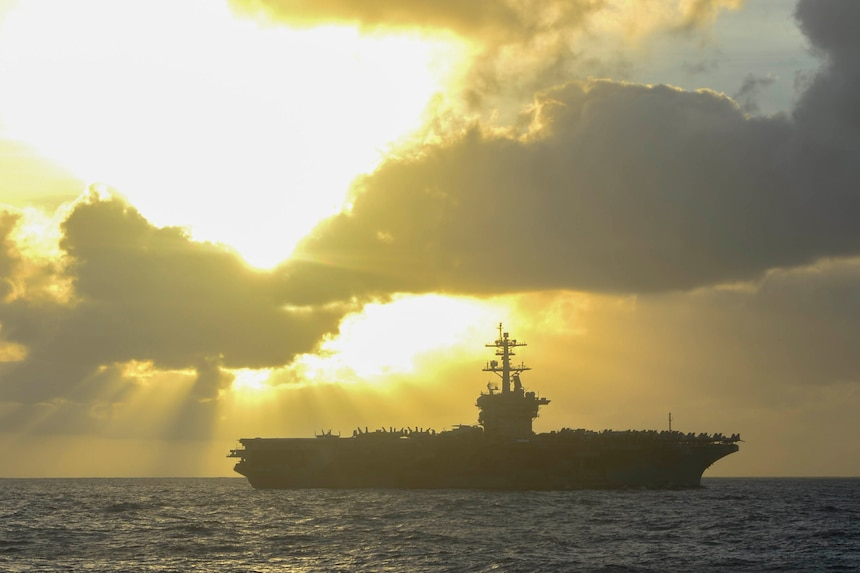 An aircraft carrier floats on the sea.