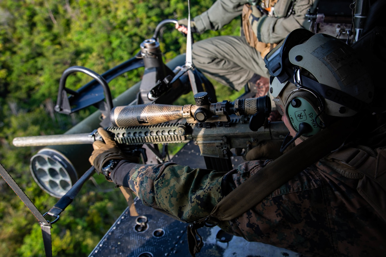 A machine gunner takes aim out of a helicopter.