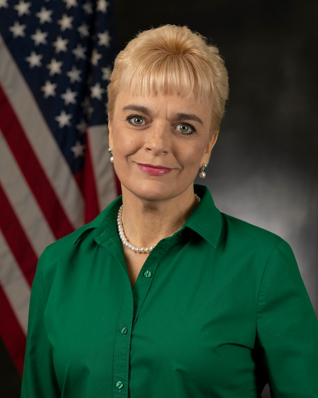 A blonde woman in a green shirt smiles and poses in front of an American Flag and grey backdrop.