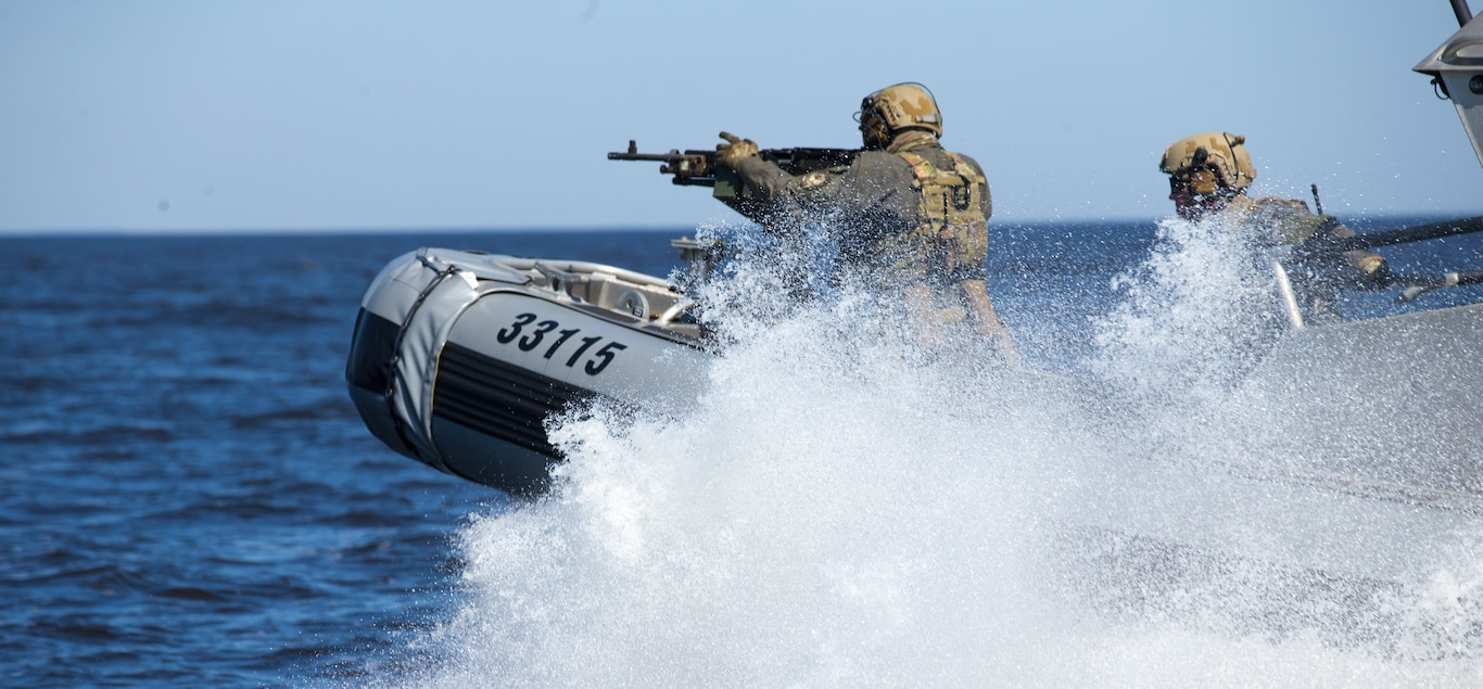 U.S. Coast Guardsmen with a Maritime Security Response Team fire an M240B machine gun from a response boat during advanced interdiction training near Bombing Target 9, N.C., March 9.