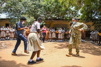 Lt. Aricka Faulkner learns a traditional dance from teachers and students at a junior high school during a community relations event in Tema, Ghana as part of Exercise Obangame Express 2021.
