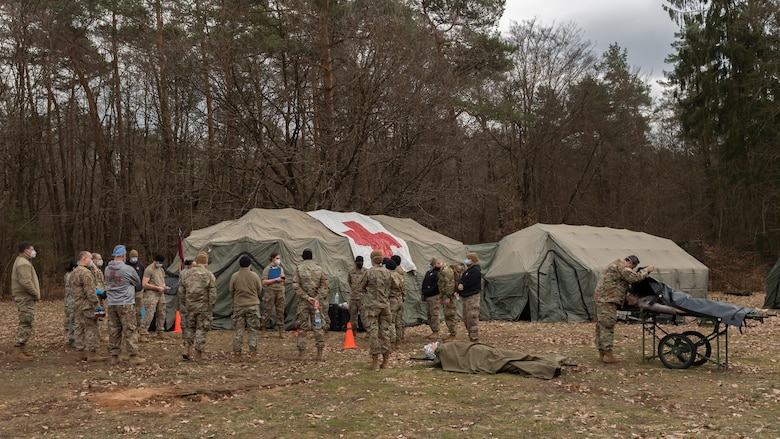 Medical personnel standing around medical tents.