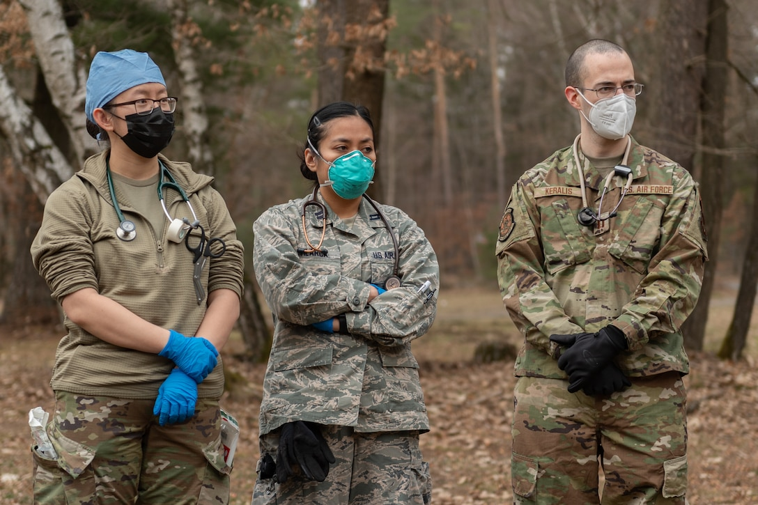 Medical personnel standing in an outdoor training area.