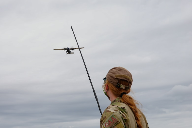 Photo of Airman looking at a plane flying