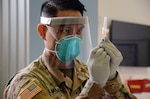 A man in a military operational camo pattern uniform holds a syringe while wearing personal protective equipment.