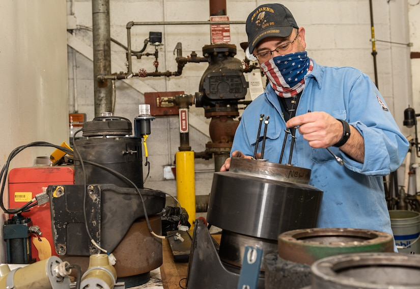 Photo of a man standing at a work bench while he repairs the wheel hub for the automated guided vehicles.