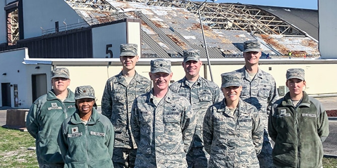 8 members of the Tyndall Legal Office standing in front of Hangar 5 after Hurricane Michael