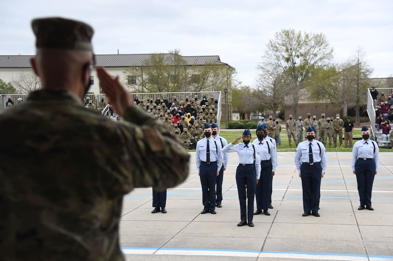 U.S. Air Force Col. Chance Geray, 81st Training Group commander, returns a salute to members of the 338th Training Squadron regulation drill team during the 81st TRG drill down on the Levitow Training Support Facility drill pad at Keesler Air Force Base, Mississippi, March 19, 2021. Airmen from the 81st TRG competed in a quarterly open ranks inspection, regulation drill routine and freestyle drill routine. Keesler trains more than 30,000 students each year. While in training, Airmen are given the opportunity to volunteer to learn and execute drill down routines. (U.S. Air Force photo by Kemberly Groue)