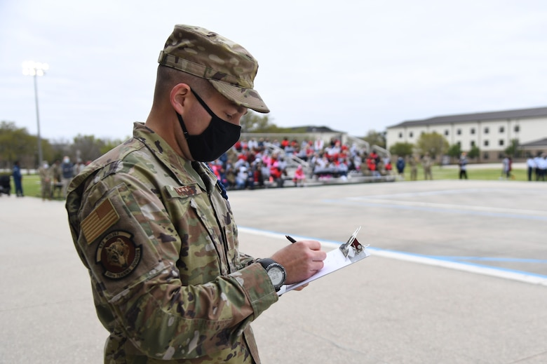 U.S. Air Force Tech. Sgt. Robert Watts, 336th Training Squadron military training leader, judges routines during the 81st Training Group drill down on the Levitow Training Support Facility drill pad at Keesler Air Force Base, Mississippi, March 19, 2021. Airmen from the 81st TRG competed in a quarterly open ranks inspection, regulation drill routine and freestyle drill routine. Keesler trains more than 30,000 students each year. While in training, Airmen are given the opportunity to volunteer to learn and execute drill down routines. (U.S. Air Force photo by Kemberly Groue)