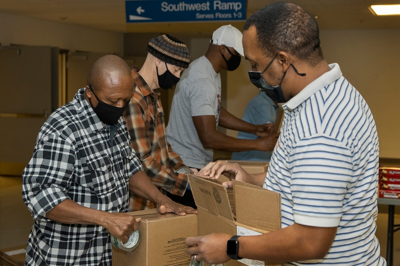 Command Sgt. Maj. Kenneth F. Law, U.S. Army Financial Management Command senior enlisted advisor, left, and Ronald Houston, USAFMCOM Army Military Pay Office site captain, right, build boxes for Soldier care packages at the Maj. Gen. Emmett J. Bean Federal Center in Indianapolis March 6, 2021. Law and Houston joined other Army Soldiers, civilian employees, veterans and retirees to make care packages, which will be sent to deployed Soldiers of the U.S. Army Reserve's 310th Expeditionary Sustainment Command. (U.S. Army photo by Mark R. W. Orders-Woempner)