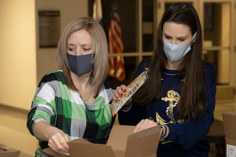 Valerie Dillion, U.S. Army Financial Management Command secretary to the general staff, left, and Liv Marvin, USAFMCOM assistant inspector general, fill Soldier care packages at the Maj. Gen. Emmett J. Bean Federal Center in Indianapolis March 6, 2021. Dillon and Marvin joined Army Soldiers, civilian employees, veterans and retirees to make care packages, which will be sent to deployed Soldiers of the U.S. Army Reserve's 310th Expeditionary Sustainment Command. (U.S. Army photo by Mark R. W. Orders-Woempner)