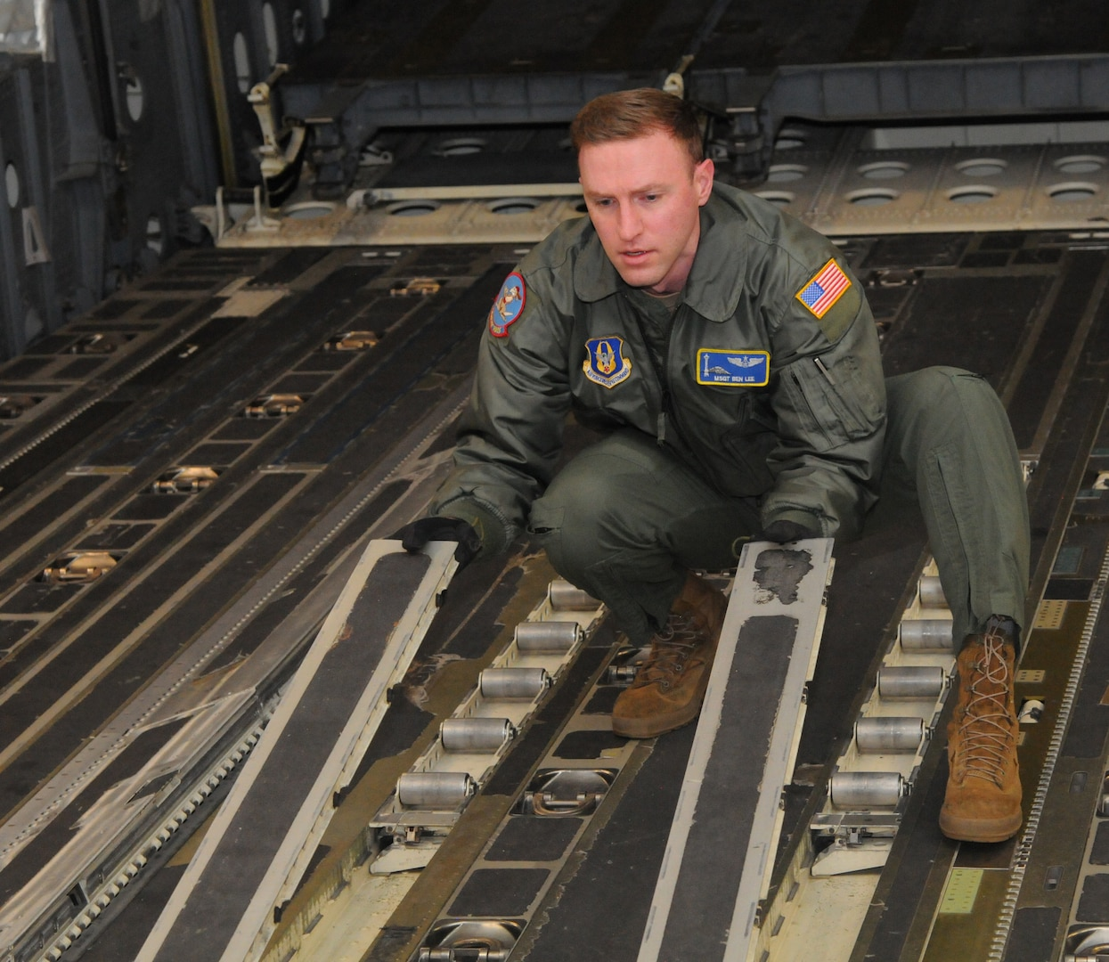 Master Sgt. Benjamin Lee, a loadmaster assigned to the 97th Airlift Squadron here, flips cargo rails rollers on a C-17 Globemaster III to prepare the aircraft for a cargo upload during a local sortie mission March 15, 2021.
