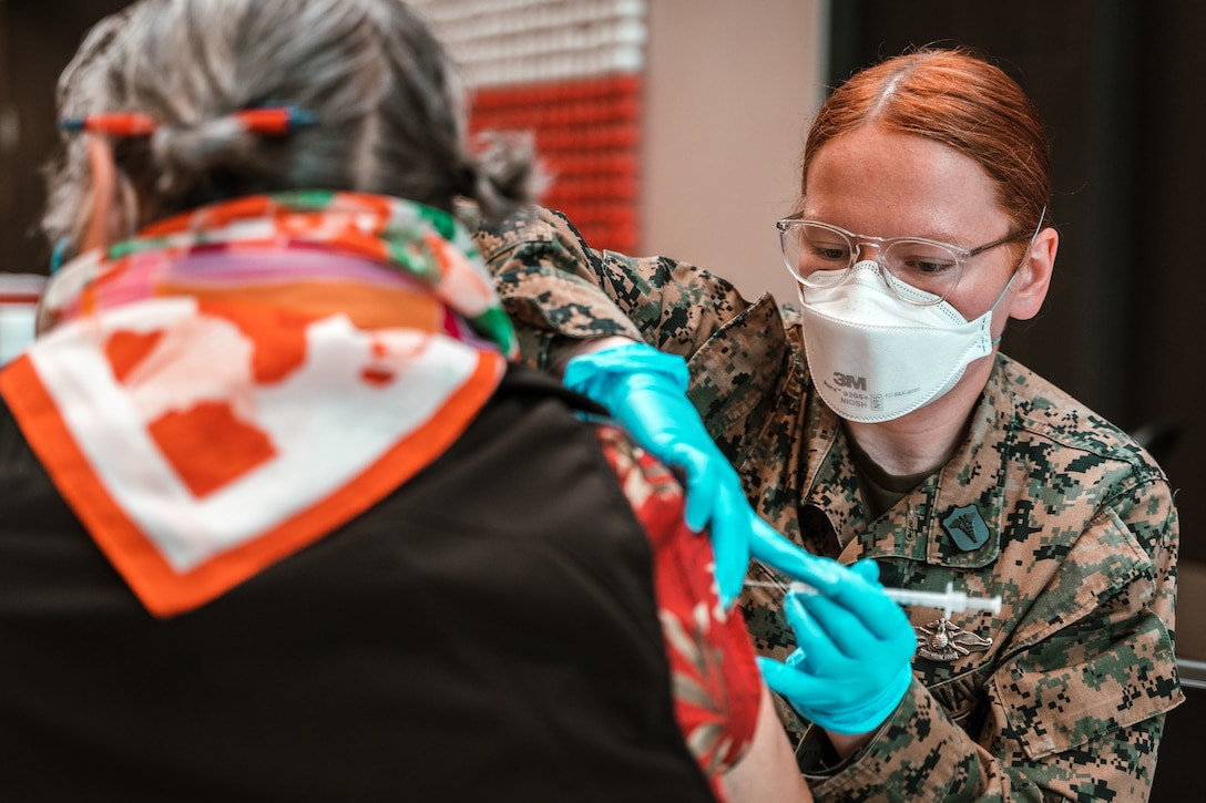 U.S. Navy Petty Officer 3rd Class, Sarah Martin, a Hospital Corpsman with 1st Marine Logistics Group (1st MLG), administers a COVID-19 vaccine to a community member at the Globe Life Field Community Vaccination Center (CVC) in Arlington, Texas, March 1, 2021. Marines and Sailors with 1st MLG, at the request of the Federal Emergency Management Agency, in partnership with the Arlington Fire Department and the City of Arlington, established a CVC located at Globe Life Field and continued administering vaccines to the Arlington community.  U.S. Northern Command, through U.S. Army North, remains committed to providing continued, flexible Department of Defense support to the Federal Emergency Management Agency as part of the whole-of-government response to COVID-19. (U.S. Marine Corps Photo by Lance Cpl. William Redding)