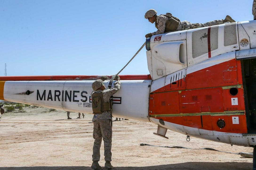 A Marine lies on top of an aircraft as another Marine stands below.
