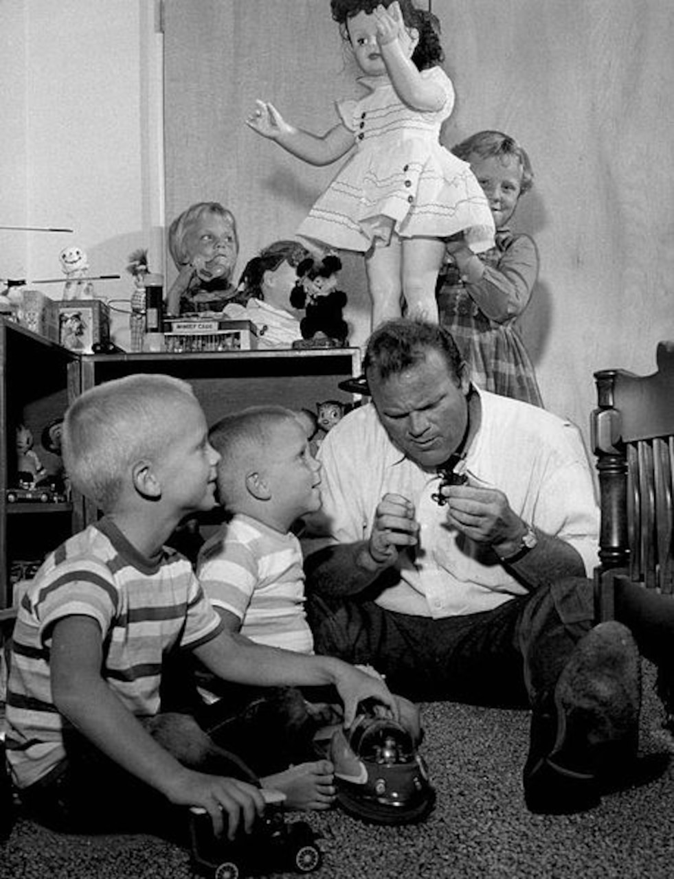 A man sits on the floor playing with two little boys as two little girls play with a large doll and other toys behind the man.